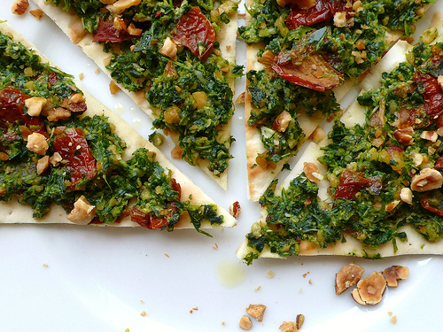 Pizza with rocket pesto, sundried tomatoes and hazelnuts