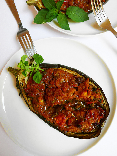 Stuffed aubergines with seitan, sun dried tomatoes, raisins, basil and mint